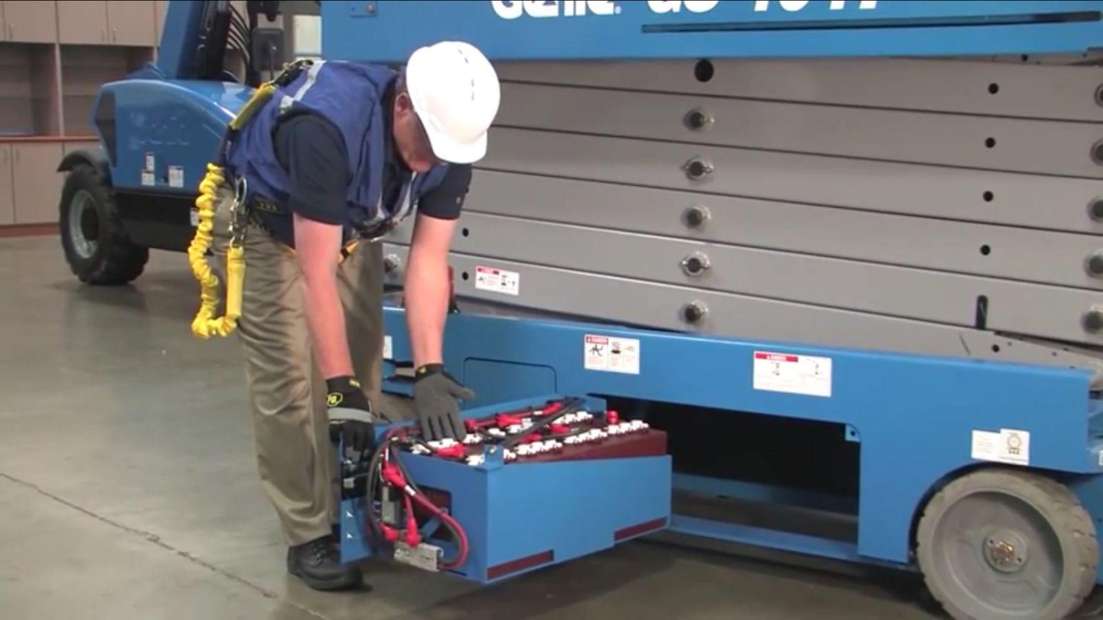 Mở hộc bình xe nâng người cắt kéo kiểm tra bình ắc quy và sạc